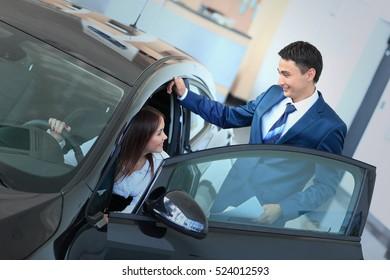 happy woman inside car in auto show or salon