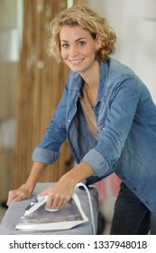 happy woman ironing clothes
