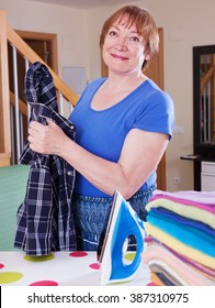 Happy woman irons a shirt on an ironing board