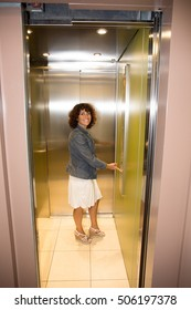 Happy woman with jacket using an elevator