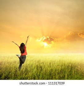 Happy woman jump in grass field and sunset