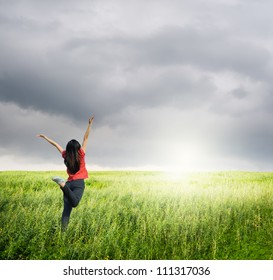 Happy woman jump in grass fields and raincloud