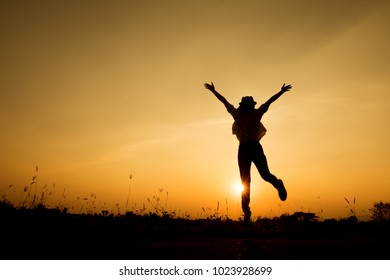 Happy woman jump and sunset silhouette with copy space.Vacation Summer concept