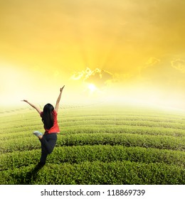 Happy woman jump in tea fields and sunset