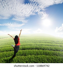Happy woman jump in tea fields and blue sky