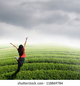 Happy woman jump in tea fields and rainclouds