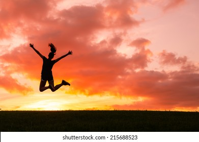 Happy woman jumping against beautiful sunset. Freedom, enjoyment concept.