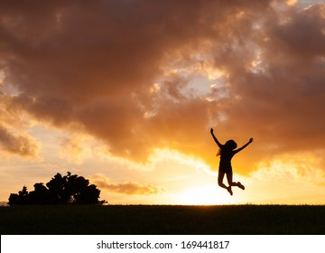 Happy woman jumping against sunset. Freedom concept. Enjoyment.