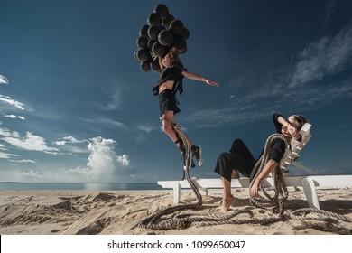 Happy woman jumping with black balloons on a sandy beach and tied to her foot by rope so as she will not fly away. Her girl friend take a rest on lounge chair.