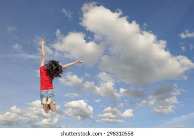 Happy woman jumping to blue cloud sky. Vacation summer concept
