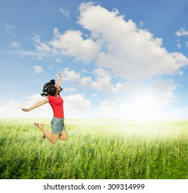 Happy Woman jumping  in green grass fields with clouds sky.Summer holiday concept.