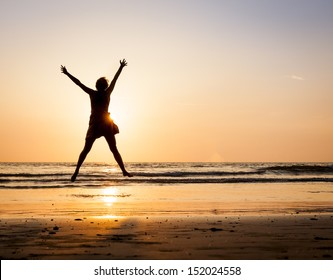 Happy woman jumping hands up on the beach at sunset with sea background