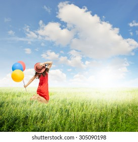 Happy Woman jumping and holding balloons  in green grass fields with clouds sky.Summer holiday concept.