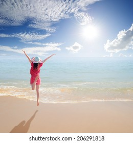 Happy Woman jumping on the beach and sun sky