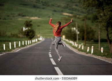 Happy Woman jumping on the country road