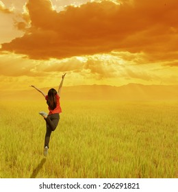 Happy woman jumping on grass field and sunset