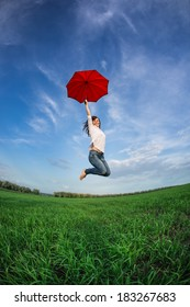 Happy woman jumping with red umbrella in green field against blue sky. Summer vacation concept