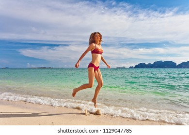 Happy woman jumping and running at the beach in the sunset rays.
