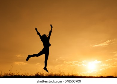 Happy woman jumping and sunset silhouette with copy space.