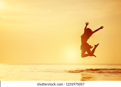 Happy woman jumps in the lake with tranquil water at sunset