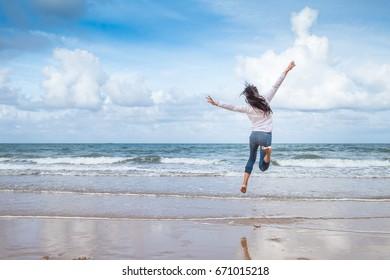 Happy woman jumps on the beach,Enjoying the Summer