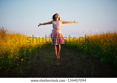 Happy woman jumps to the sky in the yellow meadow at the sunset