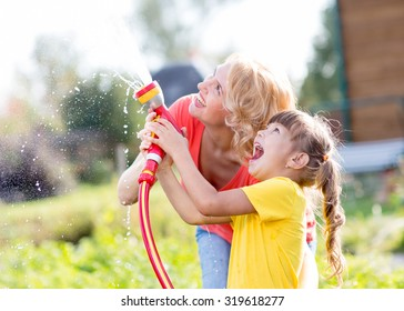 Happy woman and kid daughter watering in domestic garden at summer day