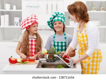 Happy woman and kids washing vegetables in the kitchen - preparing a meal together