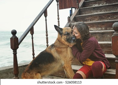 Happy woman kissing her German shepherd dog on a stairs against sea, outdoor