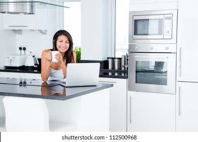Happy woman in the kitchen reading he news on her laptop