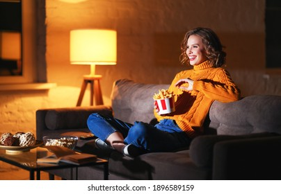 Happy woman in knitted sweater eating French fries and watching interesting movie while laughs and sitting cross legged on sofa in evening at home