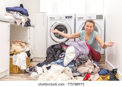 Happy woman in laudry room with a pile of dirty clothes
