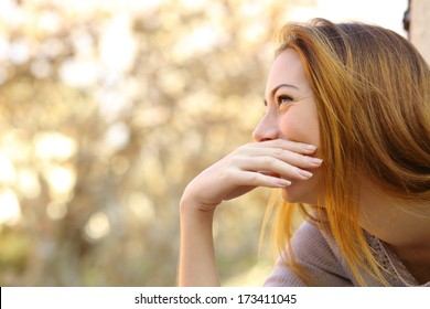 Happy woman laughing covering her mouth with a hand with a warmth background