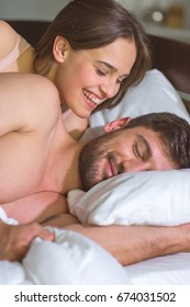 The happy woman lay with a man in the bed