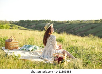 Happy Woman Life Style, beautiful relaxed girl in a straw hat on the nature picnic basket flowers in the rays of the soft sunset sun, a picnic - camping.