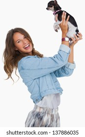 Happy woman lifting her chihuahua on white background