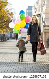 happy woman and little child with red shopping bag and air-balloons, walking on street