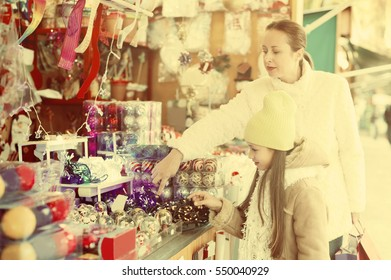 Happy woman with little daughte buying decorations for Christmas. Focus on girl