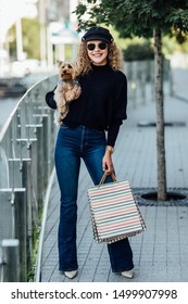 Happy woman with long curly hair holds small dog and shopping bags. Beautiful girl hugs little dog. Lady with puppy. Smiling attractive woman with Yorkshire terrier. Girl with dog in hands.