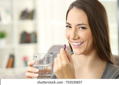 Happy woman looking at camera holding a pill and a glass of water ready to take it sitting on a couch at home