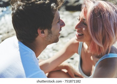 Happy woman looking at her boyfriend on beach