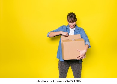 HAPPY woman looking into a cardboard box for new stuff, on yellow background