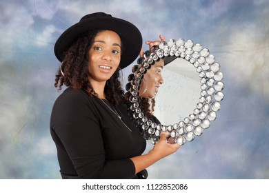 Happy woman looking into a round miror