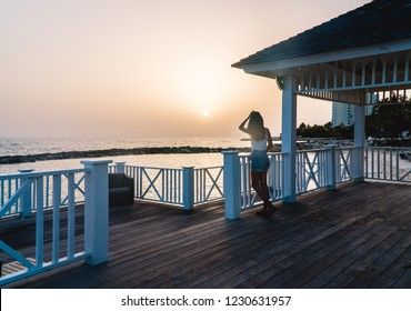 Happy woman looking out onto an orange sunset, on romantic trip to Montego Bay, Jamaica, Caribbean. Shot on oceanfront pier deck.