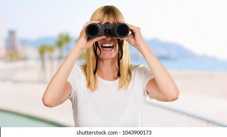 happy woman looking through binoculars, outdoor