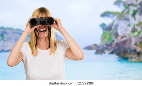 happy woman looking through binoculars at a beach
