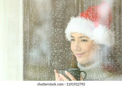Happy woman looking through a window in christmas time in a rainy day