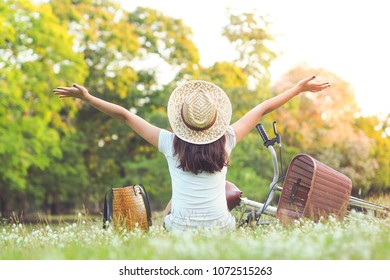 Happy woman looking at the view with arms outstretched in park, freedom and active lifestyle concept