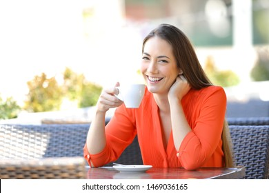 Happy woman looking at you holding coffee mug sitting in a restaurant terrace