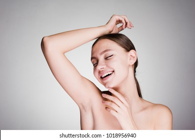 happy woman looks after armpits on a gray background